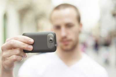 Man holding a cellphone and shooting video