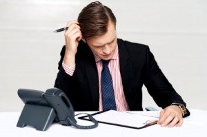 Businessman at desk, confused, scratching head