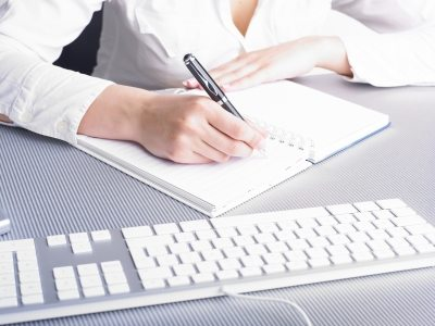 Woman sitting at desk with pen in hand writing, page is blank