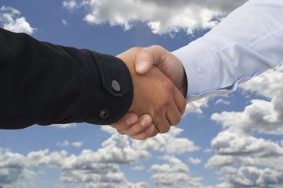 business men shaking hands with clouds in background